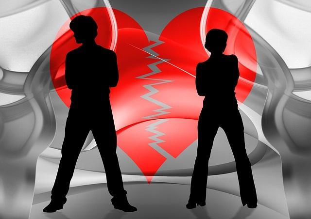 Entzweites Paar vor einem roten, gebrochenen Herz