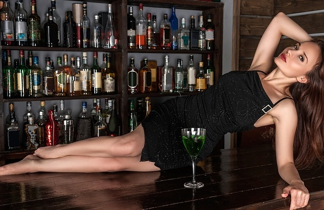 Sexy Frau im schwarzen Kleid, liegend auf einer Theke